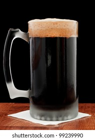 dark beer isolated on a black backgroud served in a chilled mug