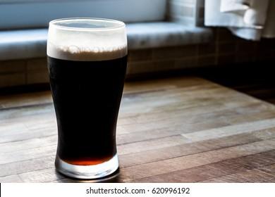 Dark Beer at kitchen on wooden surface.