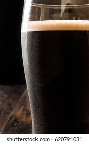 Dark Beer on wooden surface. Close up view.