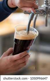 dark beer in plastic cup flowing from beer tap with nice  foam close-up in female bartender hands on blurred background