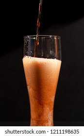 Dark beer is poured into a tall glass goblet, the beer foams heavily. On a black background.