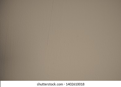 Dark beige concrete wall with randomly plastered structures and light soiling in industrial design. Pastel colored stone wall as background and design element for art. Bright dark gradients.