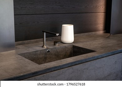 Dark beige marble wash basin with glossy metal mixer. White decorative vase. High quality photo