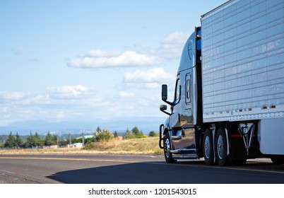 Dark big rig modern professional popular semi truck transporting perishable food in chilled refrigerated semi trailer running on divided local road with meadow view and clouds for delivery goods