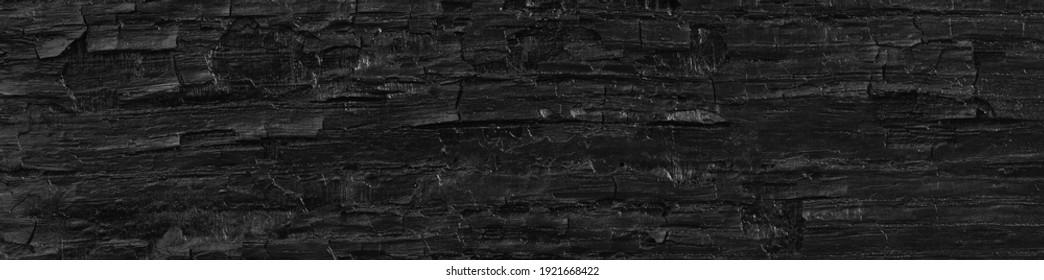 Dark black background of rough burnt wood, soot, and ash. Burn texture.