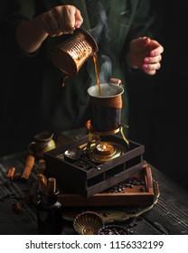 Dark black background woman makes turkish coffee cup turk aroma beans hot smoke steam coffee
