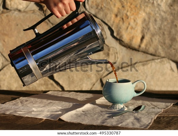 Dark, Black Coffee Being Poured From Vintage Metal Coffee Percolator  Into Blue Ceramic Cup On Wooden Table  With All Natural Cotton Linen Tea Towel And Spoon And Large Stone Background