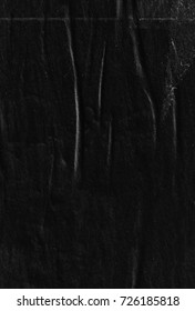 Dark black paper background creased crumpled texture / Old torn ripped posters scary grunge