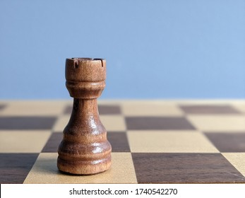 Dark/ Black  Rook chess piece isolated on a wooden chess board. Strategic placement and play. Rich brown and white checkered board. Mind using boarding games with tactics and skills.