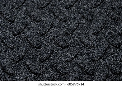 Dark Black Rough Texture / Image showing a closeup view of black spray on bed liner material with a diamond pattern underneath.