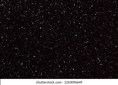 Dark black sparkling background from small sequins, closeup. Brilliant shiny backdrop from textile. Shimmer paper