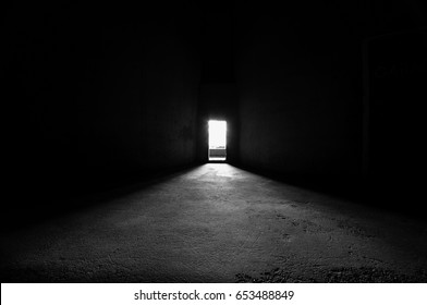 Dark black and white image inside of a silo facing a bright door way.