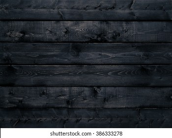 Dark black wood texture background viewed from above. The wooden planks are stacked horizontally and have a worn look. This surface would be great as design element for a wall, floor, table etc.