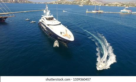 dark ble mega yacht and tender at marina