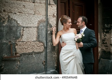 Dark blonde bride looks over her shoulder at groom while they stand on ruined street