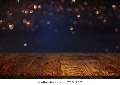Dark blue background with bokeh and a empty wooden table  for a festive concept