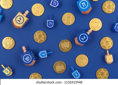 Dark blue background with multicolor dreidels and chocolate coins. Hanukkah and judaic holiday concept. Horizontal