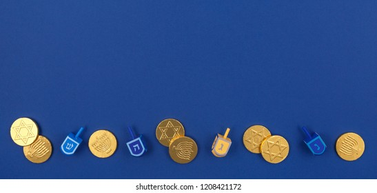 Dark blue background with multicolor dreidels and chocolate coins at the bottom. Hanukkah and judaic holiday concept. Horizontal, wide screen banner format