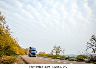 Dark blue bonnet modern American big rig classic freight transportation bonnet semi truck with black grille transporting commercial cargo in dry van semi trailer on the winding autumn local road