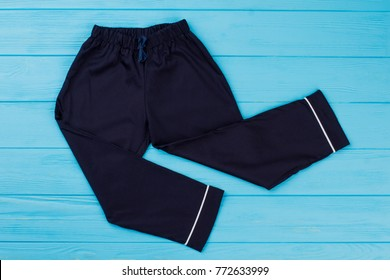 Dark blue boys' pants with white stripes on wooden background. Classic pajama's bottom.