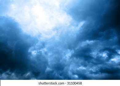 dark blue cloudly sky with ray of sunlight after storm