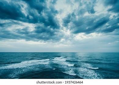 Dunkelblaue Wolken und Meer- oder Meereswasseroberfläche mit Schaumwellen vor Sturm, dramatische Jahreszeiten