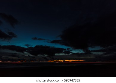 Dark blue cloudy sky over the Baltic sea at night