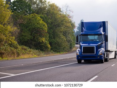 Dark blue day cab big rig semi truck fleet for community local deliveries of goods to the stores with dry van semi trailer running on wide highway with green and yellow trees