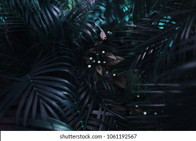 dark blue exotic fantastic portrait of turquoise palm leaves and flower. concept of travel, phone or laptop wallpaper background