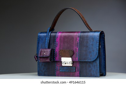 Dark blue female leather bag with reptile skin details isolated on grey.