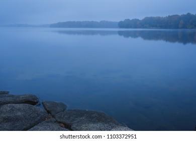 dark blue foggy morning on the lake
