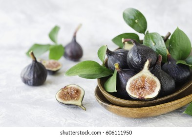 dark blue Fresh figs in a wooden bowl with greens on a white marble table, selective focus