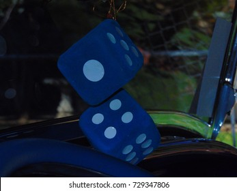 Dark blue fuzzy dice hanging from a rear view mirror in a car