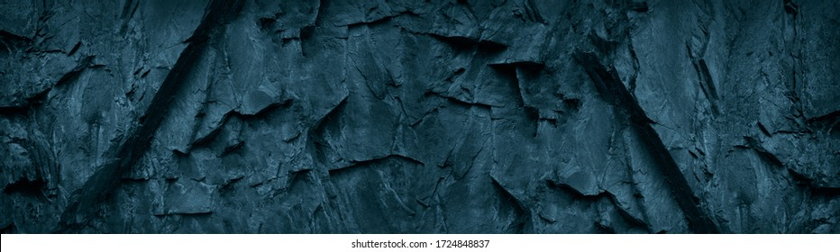 Dark blue green stone background. Grunge background. Banner with toned rock texture. The combination of teal color and rough mountain texture.