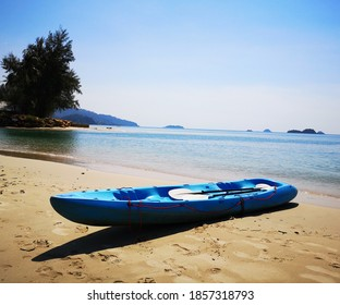 Dark blue kayak boat on a sandy beach in Thailand. Travel and tourism concept in Southeast Asia. Wallpaper, brochure, banner, poster, flyer and template.