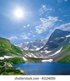 dark blue lake in a mountains under a sun