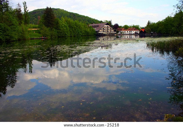 dark blue lake with restaurants in the background. skies and clouds reflected on the water