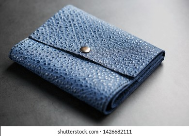 Dark blue leather wallet on a dark background top view. Close-up, purse details, rivet and firmware