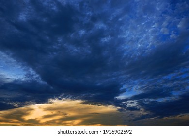 Dark blue orange abstract background. Yellow golden sunset. Beautiful cloudy sky at sunset. Navy blue sky background with copy space for design.