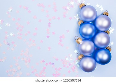 Dark blue and pastel ble Christmas ball on a pastel blue background with pink stars confetti. Place for your design.