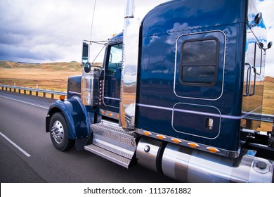 Dark blue shiny classic American big rig semi truck with chrome accessories with reflection on cab surface running on the road with yellow summer field on background in California