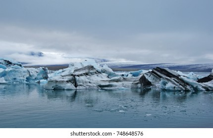 dark blue sky over the colorful icebergs of the Vatnajakull Glacier in Iceland. The Icebergs are blue, white gray and black-strips colored