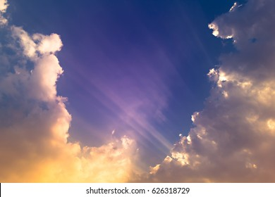 Dark blue sky with purple sun ray light and orange clouds