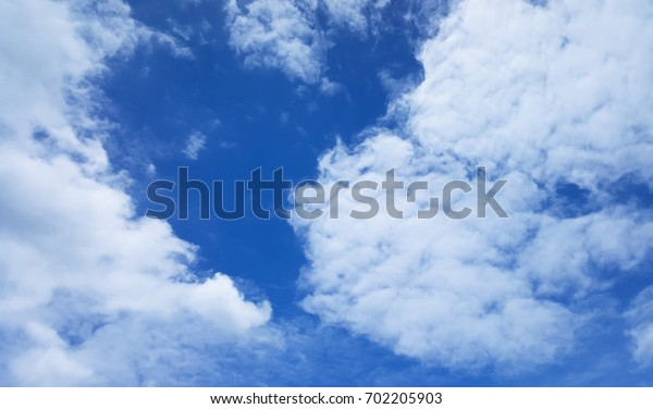 Dark blue sky with white clouds look like a heart.