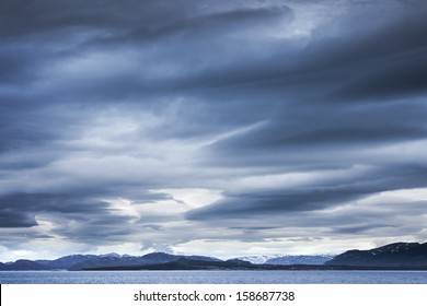 Dark blue stormy clouds over the mountains. Empty Norwegian sea landscape