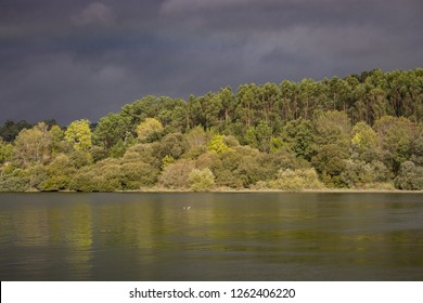 Dark blue stormy sky over river and forest on bank. Nature before storm. Beautiful river landscape. Meteorology and weather concept. Dramatic moody landscape before thunderstorm.