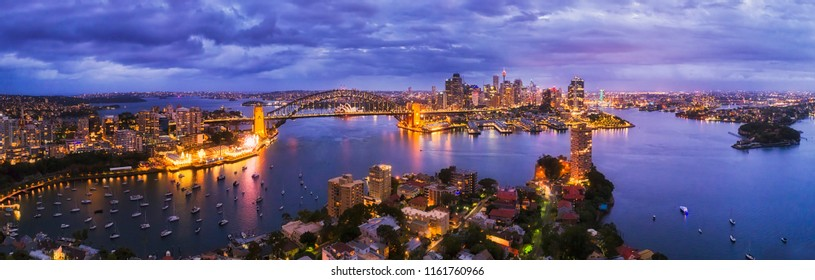 Dark blue sunset over Sydney city on Sydney harbour shores from North to city CBD connected by Harbour bridge in elevated aerial wide panoramic view.