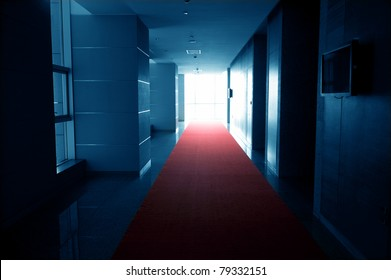 Dark blue tone of long hall with red carpet.