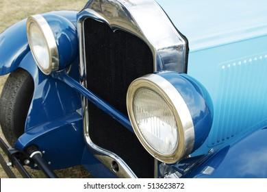 Dark blue vintage car on a festival of old cars. Retro car's headlight close up.