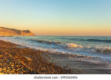 Dark blue waves against the beautiful orange sunset at the Black Sea, Anapa, Russia